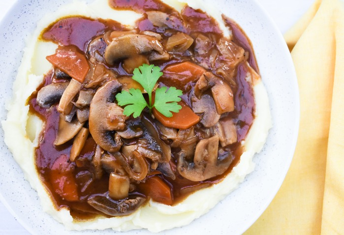 A close up of mushroom stew over mash in a bowl