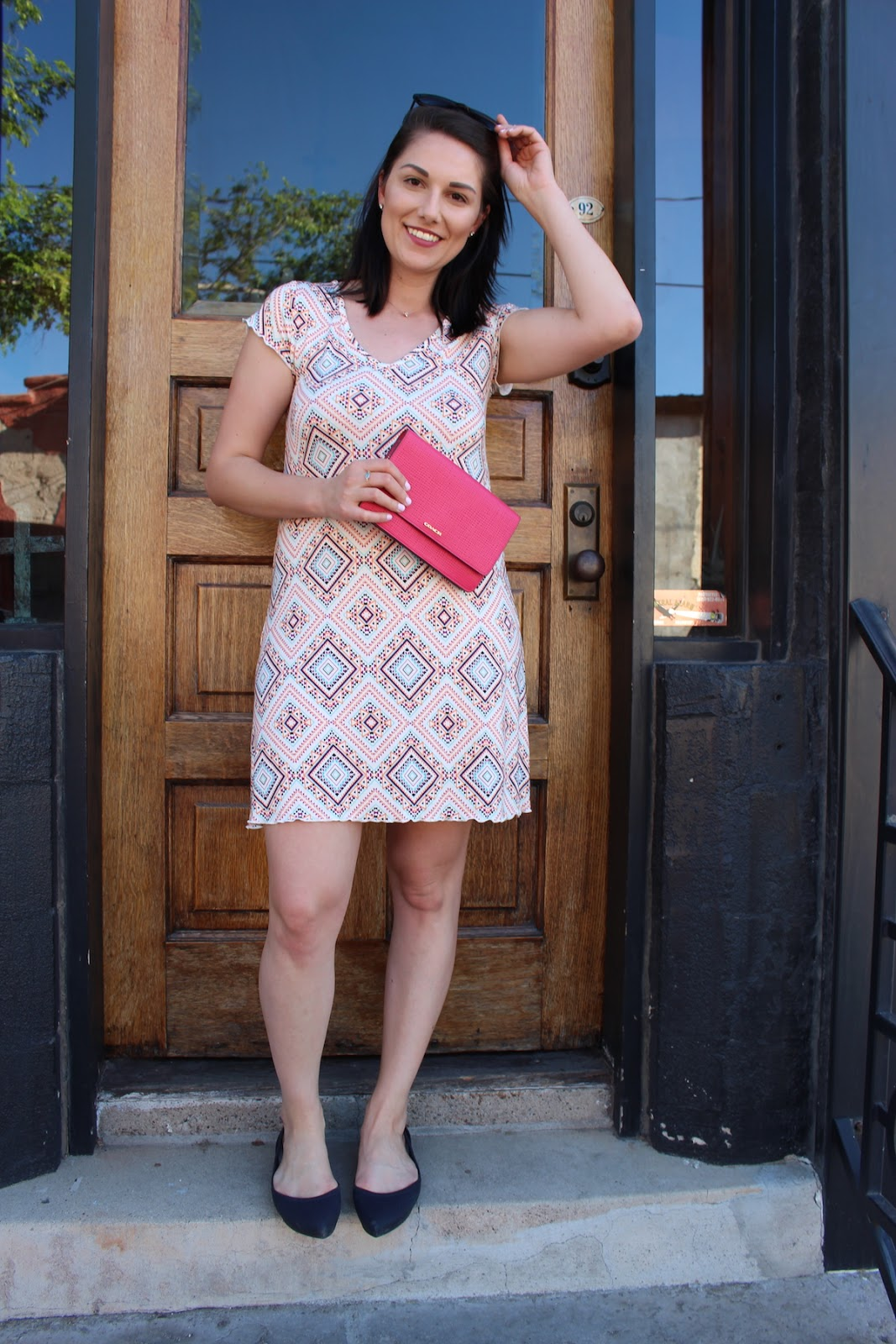 This is a close up of me wearing a Stitchfix white dress with many colors, holding a pink clutch.