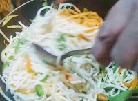 Mixing hakka noodles with spoon and fork for hakka noodles veg recipe