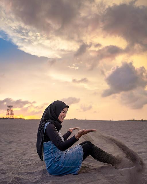 cewek sedang bermain pasir di gumuk pasir parangkusumo jogja