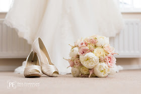 wedding bouquet of pink and ivory roses and peonies and ivory wedding shoes