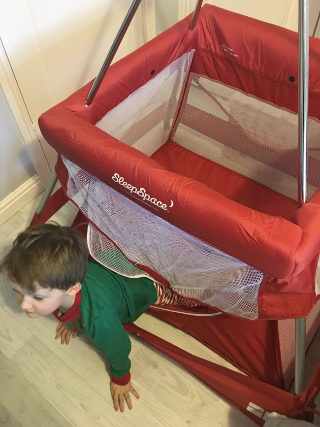 Babyhub-sleepspace-travel-cot-child-climbing-out-of-cot-through-zipped-side