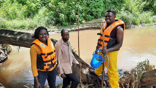 Three research assistants stand by a river wearing PPE and holding instruments