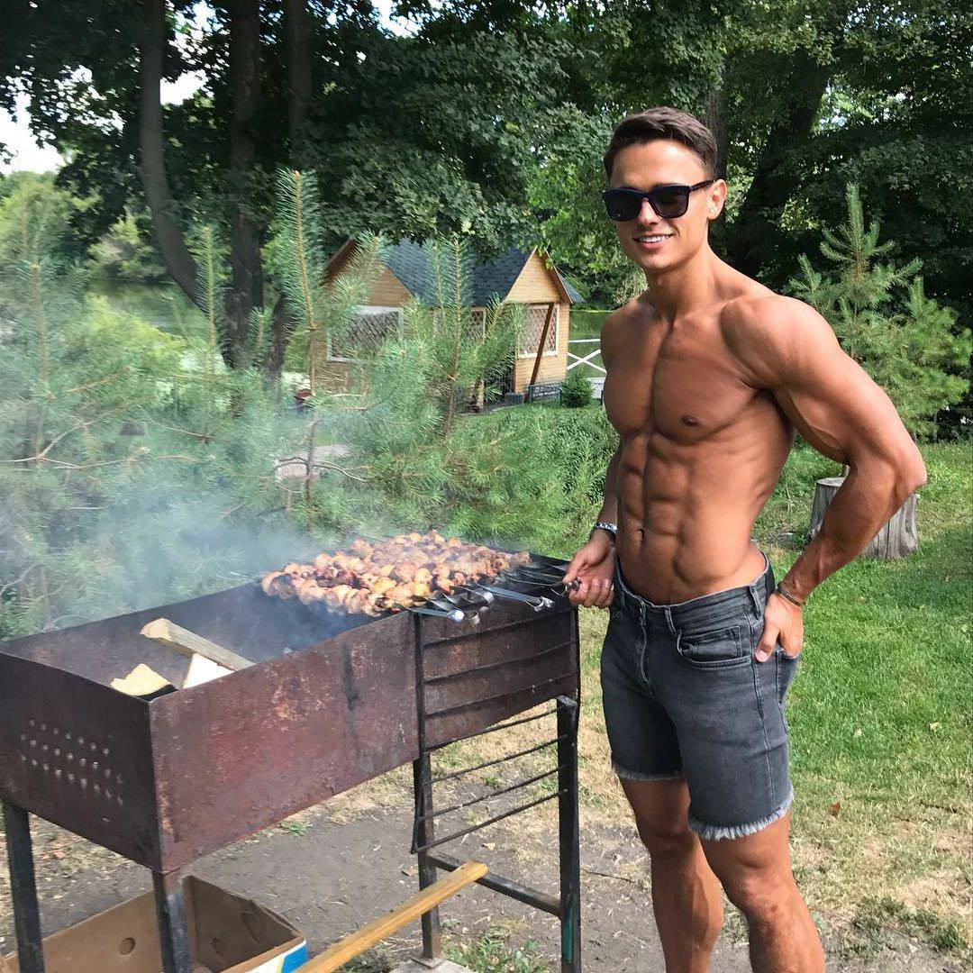 cute-shirtless-male-model-slim-fit-body-abs-gay-twink-smiling-sunglasses-grilling-meat-backyard