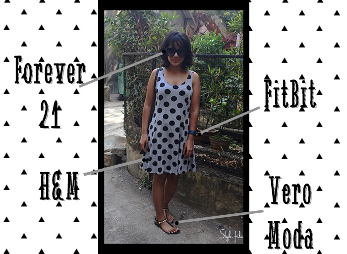 Image of female indian fashion blogger wearing grey polka dot dress with black accessories, sunglasses and pink lipstick