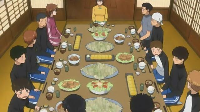 todos en una gran mesa, numerosos platos en ella, destacan ensaladas y platos con repollo