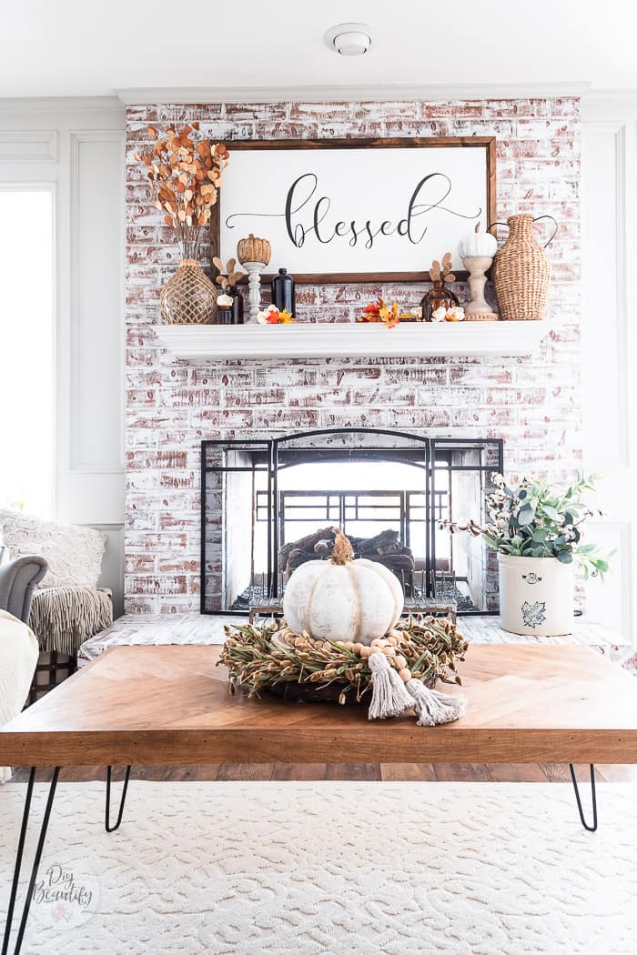 chalk painted fireplace dressed for fall and mantel with fall foliage, amber bottles and wood pumpkins