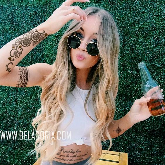 Chica rubia con gafas de sol bebiendo un refresco frente al seto de una casa, lleva tatuajes bohemios