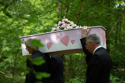 Jessica's casket being carried through the woods at GreenAcres