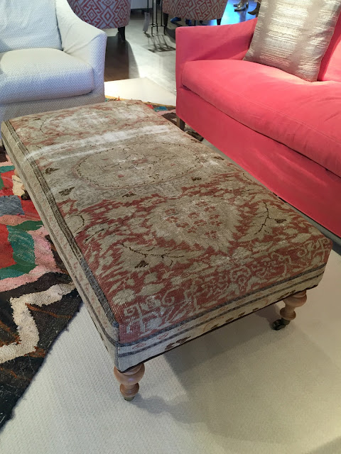 A vintage style bench upholstered in a well worn piece of a rug