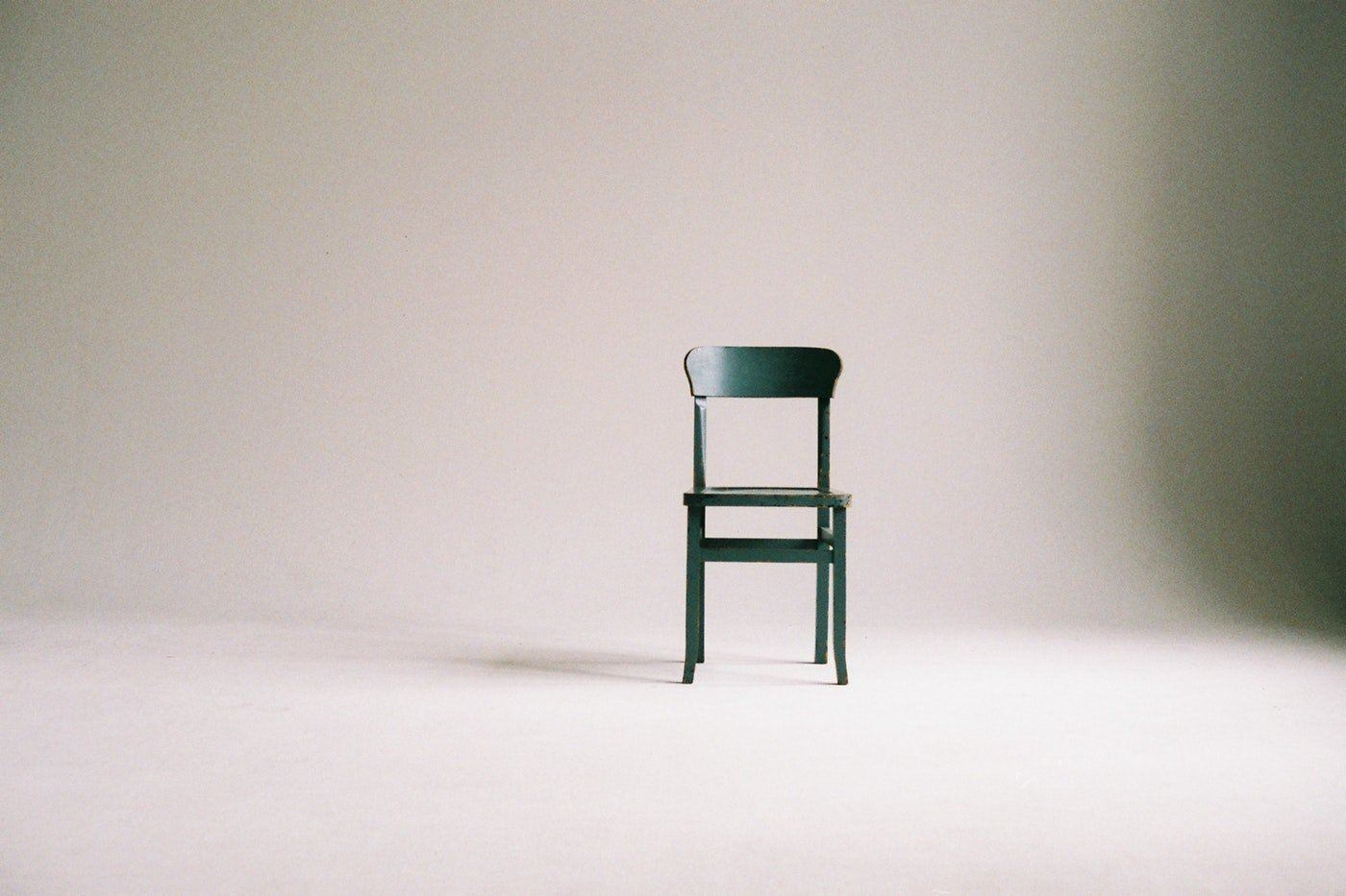 green wooden chair against white background - how our sedentary lifestyles are harming us