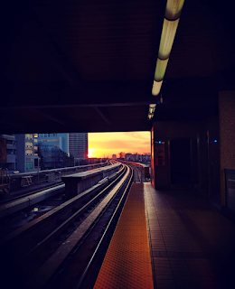 a sunset in the distance, a subway platform in the forground