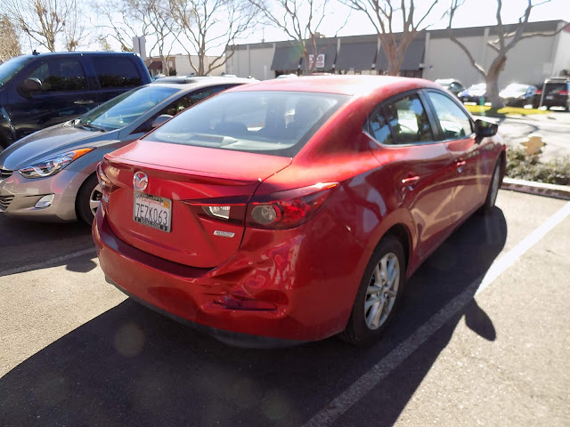 Mazda 3 with crushed bumper & 3-stage Soul Red paint before repairs at Almost Everything Auto Body.