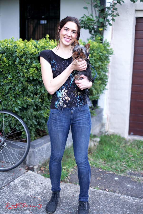 Woman holding terrier, blue jeans and black tee shirt with Pegasus print. South Newtown - Photo by Kent Johnson.