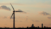 A wind turbine stands, generating power next to Hull, Mass. (Credit: AP Photo/Stephan Savoia, File) Click to Enlarge.