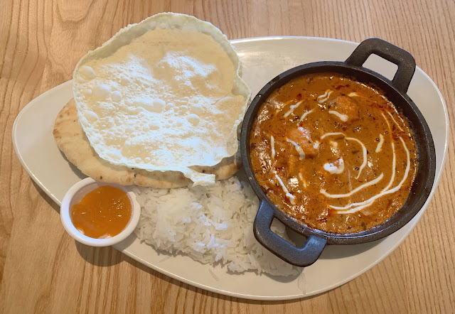 bowl of chicken tikka curry with boiled rice, nan and mango chutney