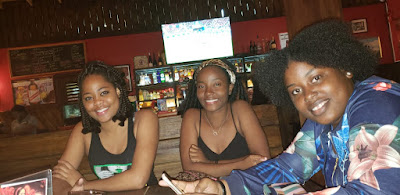 three girls sitting at the bar at lovers leap, Chevy Takes The Mic Jamaican Travel Blog Series Adventures in St. Elizabeth Jamaica, things to do in Jamaica