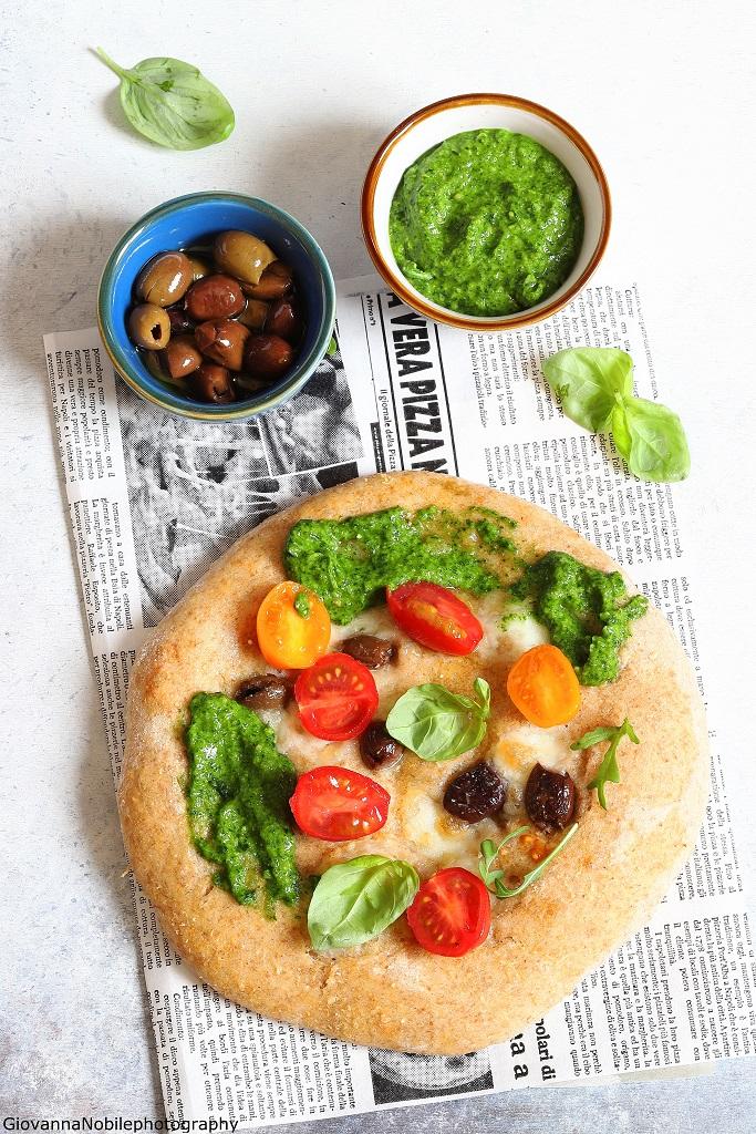Pizza con mozzarella, pesto di rucola e pomodori
