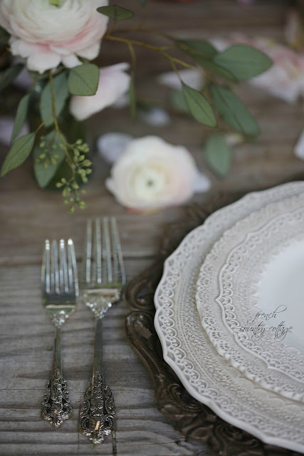 Lace dishes on weathered table with silver flatware