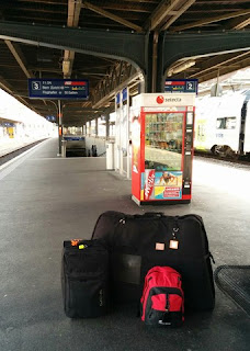 Bike bag, suitcase, and backpack on the train platform in Fribourg, Switzerland