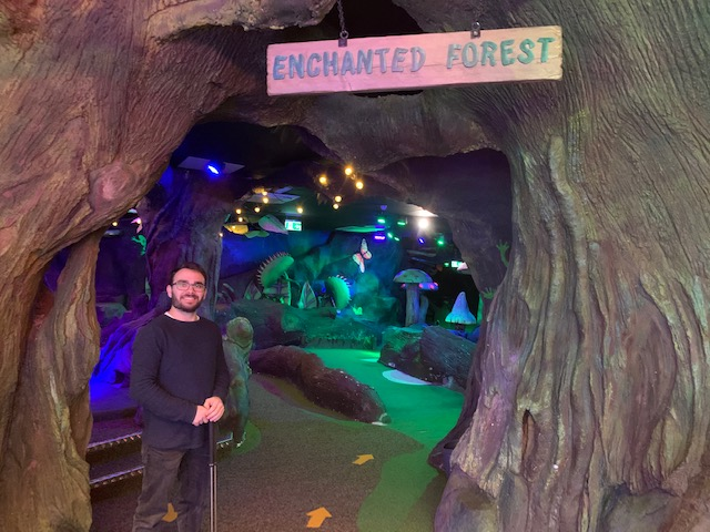 Man standing at entrance to Enchanted Forest crazy golf course