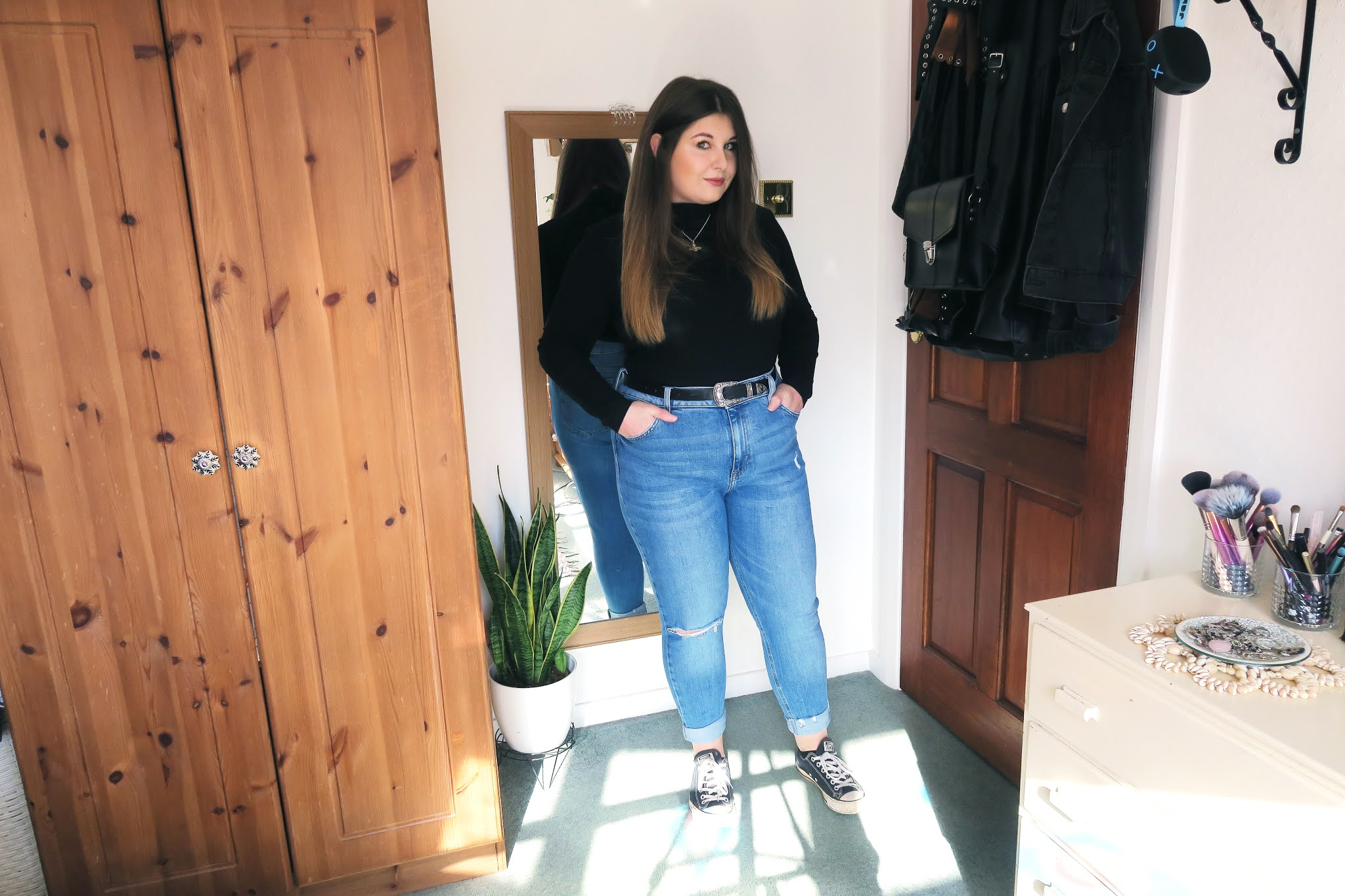 Grace is wearing a black roll neck top tucked into a pair of blue high waisted jeans. On her feet she is wearing a pair of black converse.