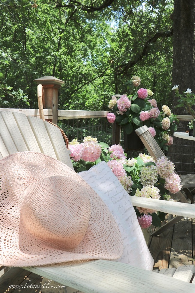 Peach straw hat and French script pillow invite resting while looking at pink hydrangeas on the deck
