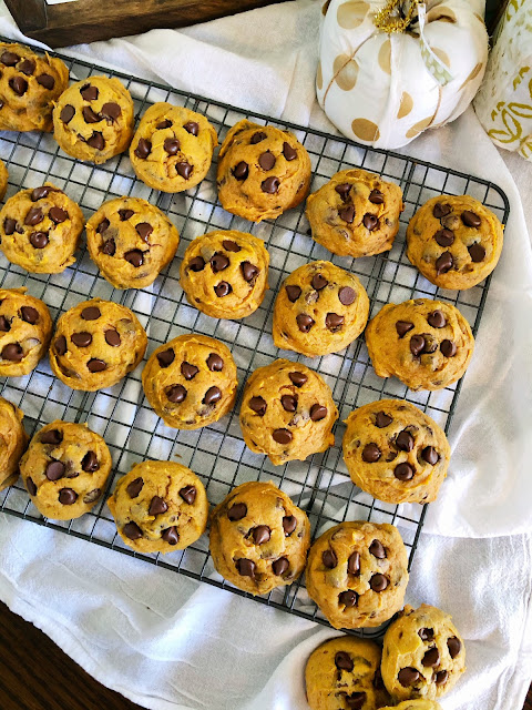 pumpkin chocolate chip cookies on a cooling rack placed on a white cloth