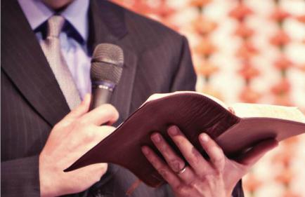 A imagem mostra um homem bem vestido segurando uma bíblia e um microfone em sua pregação para o público.