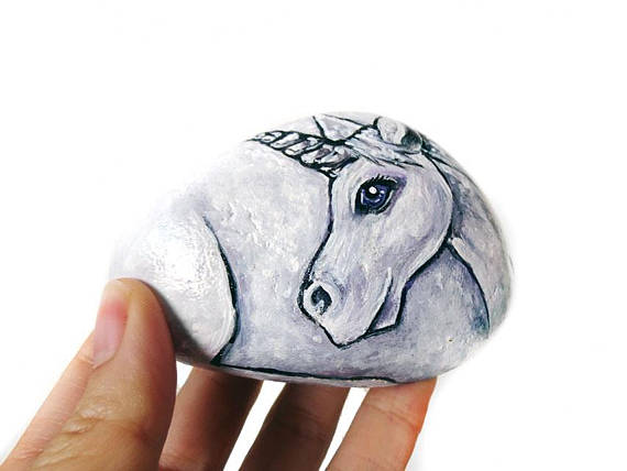 rock painted like a unicorn lying down