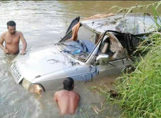 Warga memberikan pertolongan pada penumpang mobil yang masuk ke sungai.