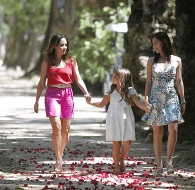 Ana veste vermelho, com Julia e Manu passeando no parque