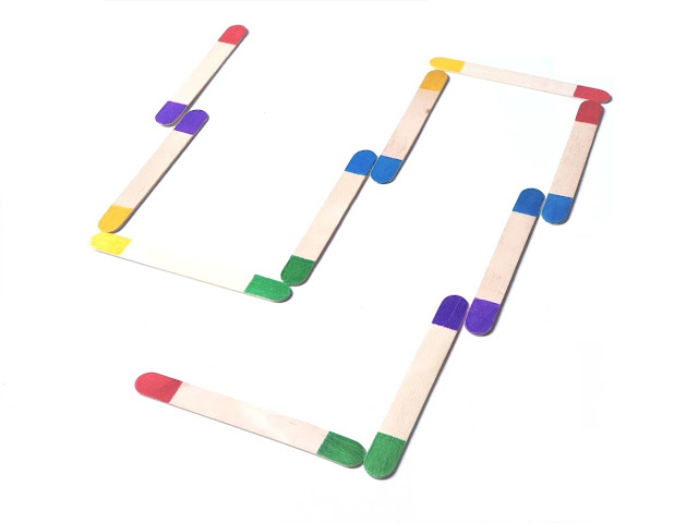 na zdjęciu drewniane patyczki laryngologiczne z pomalowanymi na różne kolory końcówkami, ułożone jak domino czyli stykające się końcami w tych samych kolorach