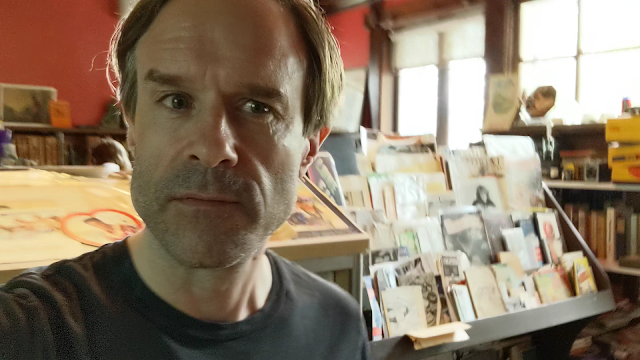 picture of guy surrounded by vintage books