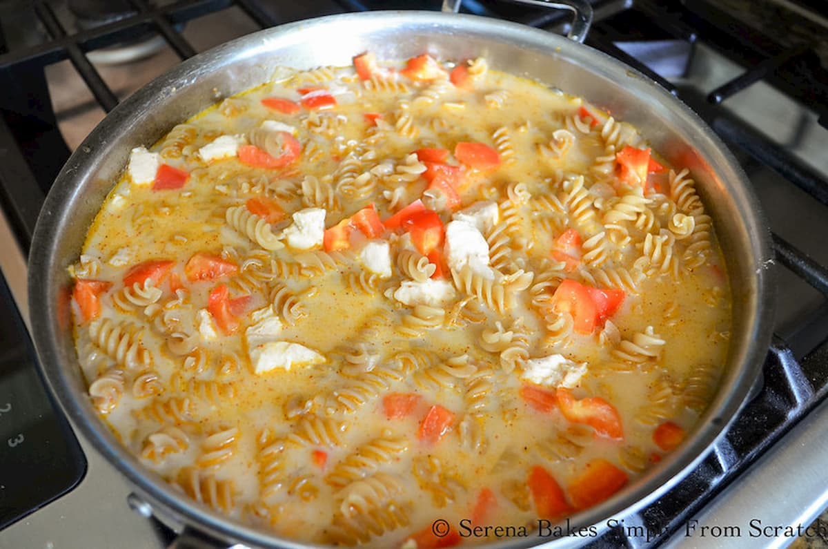 Chicken, Bell Pepper, Pasta, Chicken Stock, and Half and Half in a stainless steel pan.