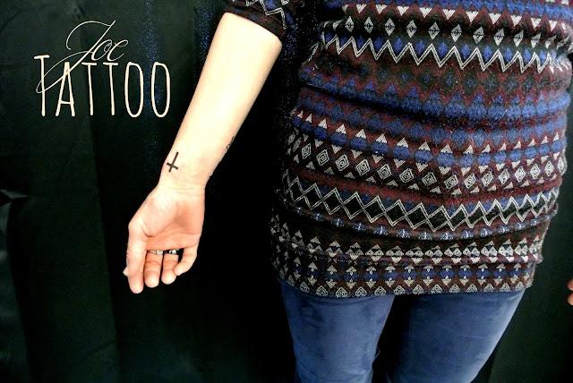 tatouage d'une fine croix chrétienne noire sur le poignet