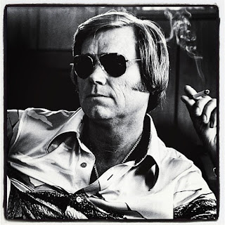 Photo of Country music singer George Jones wearing sunglasses and holding a cigarette.