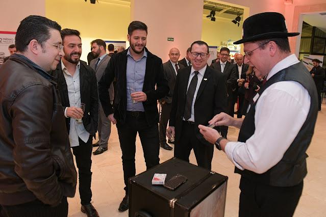 Mágico apresentando um truque em uma mesma com uma roda de convidados durante o coquetel de relacionamento do evento de premiação da Abigraf em São Paulo.