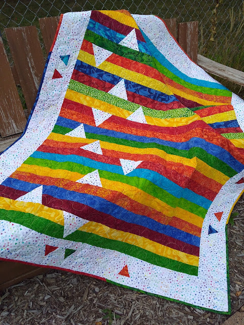 Quilt made of strips of bright colors, with inset accent triangles