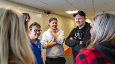 Grupp av ungdomar som står och pratar med varandra i skolkorridoren.