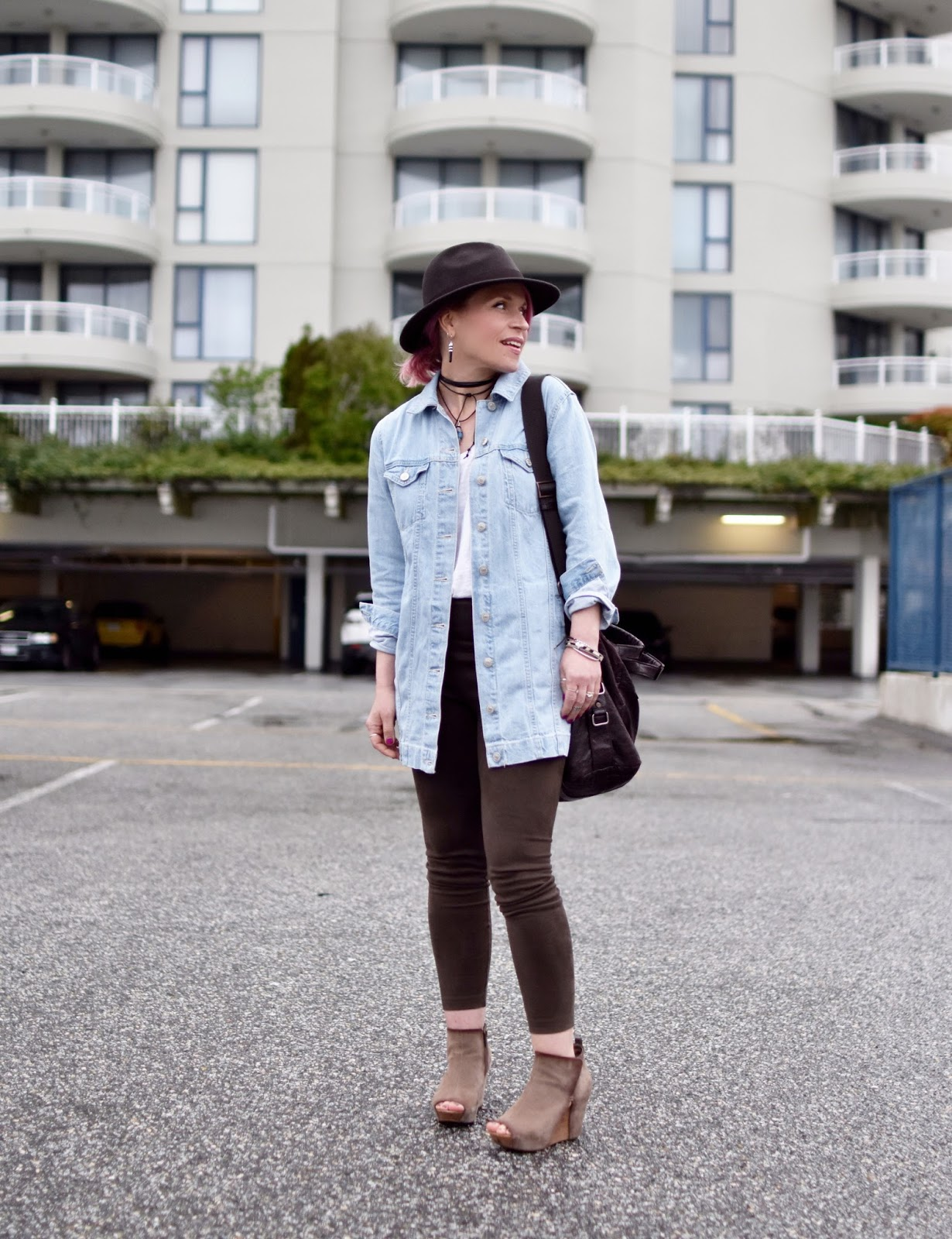 Monika Faulkner outfit inspiration - styling vegan suede leggings with an oversized denim jacket, open-toe wedge booties, and a felt fedora