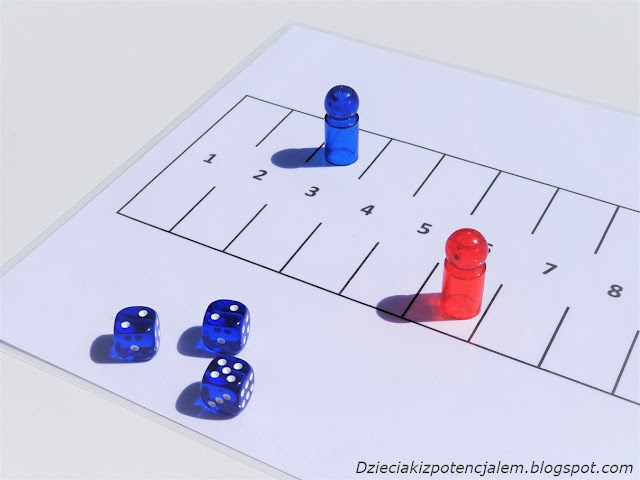 na zdjęciu plansza do gry Marinetti w kształcie prostokąta z 12 polami, na polu nr 6 stoi czerwony pionek, na polu nr 3 stoi niebieski pionek a na pierwszym planie widać trzy niebieskie kostki z wynikami  2,2,5