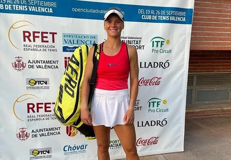 Laura Pigossi pousa para foto antes de entrar para quadra; ela tem um banner atrás de si