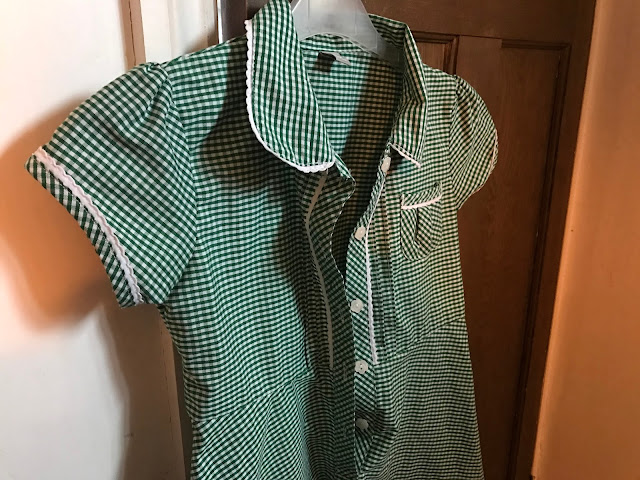 A green checked Sainsburys school summer dress with buttons hanging on a door handle