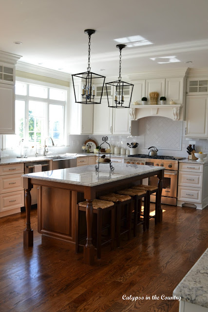 White Kitchen with Wood Floors and Cherry Island