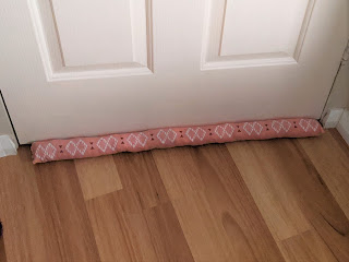 A closed door from the other side, also with a pink fabric snake.