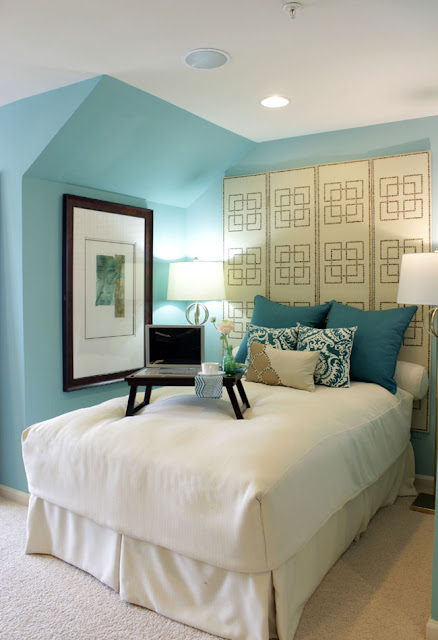 bedroom with blue walls, room divider used as headboard, white bed