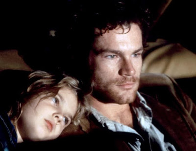 Drew Barrymore leans on David Keith's shoulder while they are on the run in a movie scene from 1984's horror film Firestarter