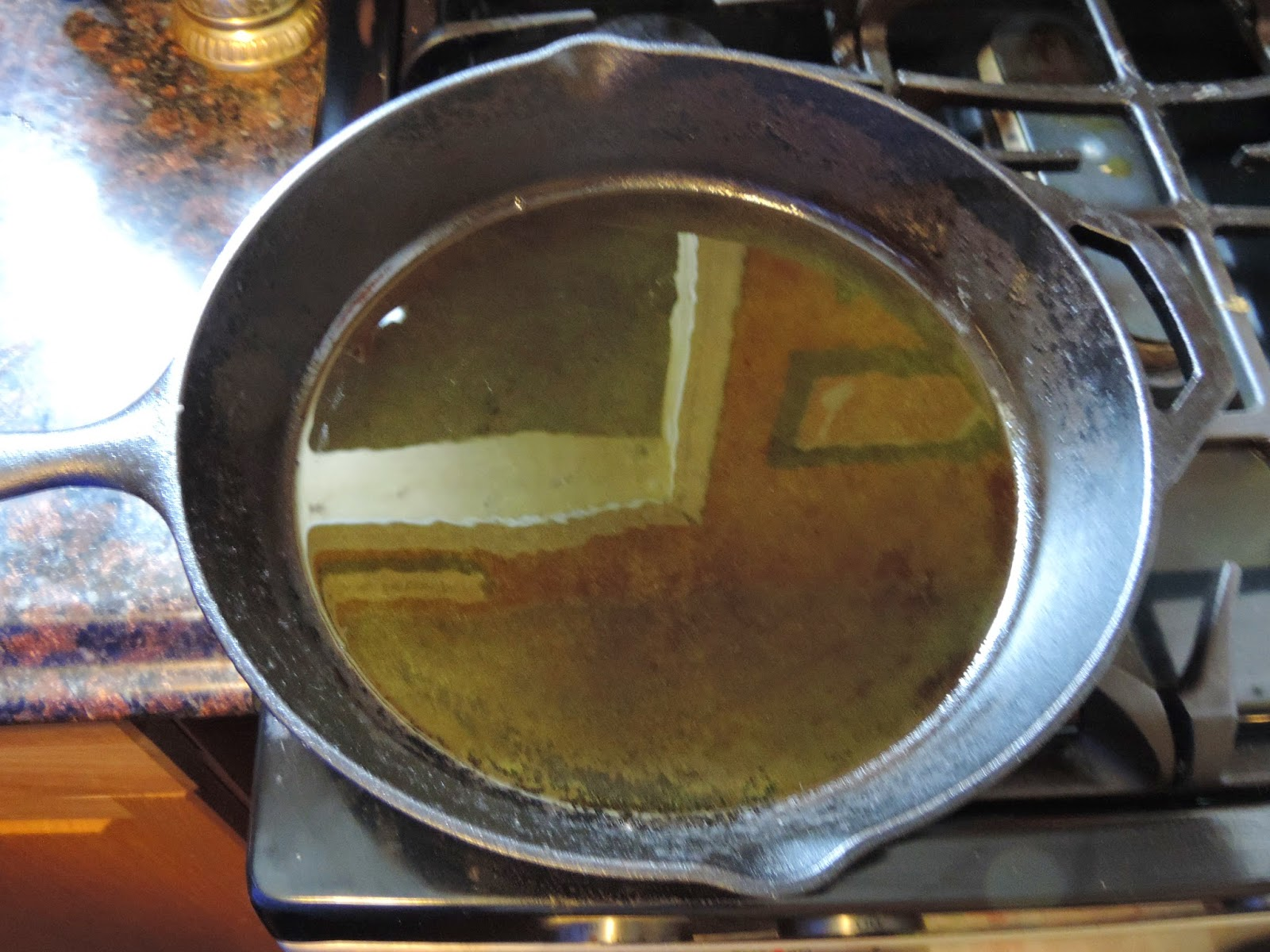 A cast iron skillet, on the stove, with oil in it.