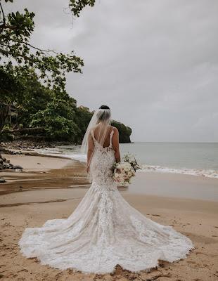 Novia con la cola del vestido extendida sobre la arena húmeda de la playa